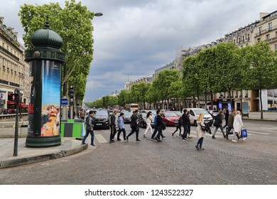Paris, France - May 13, 2018: People cross the road on the Avenue des Champs-Elysees in Paris, France on May 13, 2018