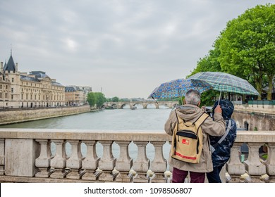 Paris / France - May 14, 2018: Beautiful older couple takes a selfie in the rain over the Seine River, with colorful umbrellas. Millions visit Paris yearly.