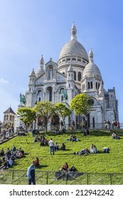 PARIS, FRANCE - MAY 15, 2014: Tourists stroll in Montmartre near Basilica Sacre Coeur (designed by Paul Abadie, 1914) - Roman Catholic Church and minor basilica, dedicated to Sacred Heart of Jesus.
