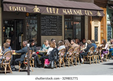 PARIS, FRANCE - MAY 15, 2014: People having lunch outdoors sit on a typical bistro on the street.