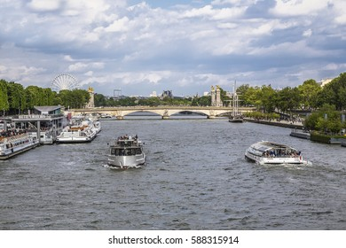 PARIS, FRANCE - MAY 15, 2016: Seine river with pleasure boats on the background of the bridge Alexander 3, and Louvre. Paris. France