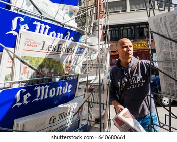 PARIS, FRANCE - MAY 15, 2017: Black ethnicity man buying Le monde newspaper reporting handover ceremony presidential inauguration of the newly elected French President Emmanuel Macron in Paris, France