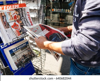 PARIS, FRANCE - MAY 15, 2017: Black ethnicity man buys Liberation with Good Luck to Macron text newspaper reporting handover ceremony presidential inauguration of the French President Emmanuel Macron