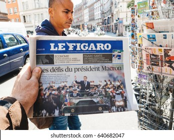 PARIS, FRANCE - MAY 15, 2017: Le Figaro newspaper with black ethnicity man buying newspaper reporting handover ceremony presidential inauguration of the newly elected French President Emmanuel Macron