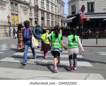 Paris, France - May 15, 2018: French children with special clothing cross the street in Paris, France on May 15, 2018