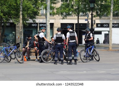 Paris, France - May 15, 2018: French policemen on bicycles check a group of men sitting on the Place de la Republique in Paris, France on May 15, 2018