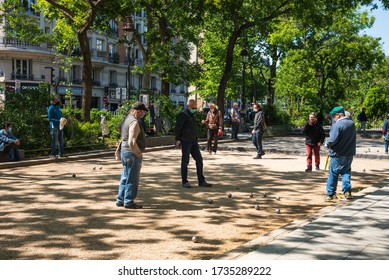 Paris, France - May 15, 2020: Senior people wearing protective masks keeping social distance play petanque at boulevard. Coronavirus lockdown end, start of deconfinement (easing restrictions).