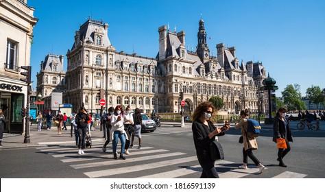 Paris, France - May 15, 2020: People wearing protective masks cross street near Hotel de Ville (City hall) square, walk for shopping. Coronavirus lockdown end, deconfinement start.