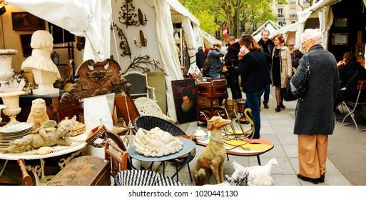 PARIS, FRANCE - MAY 16, 2016: Senior elegant woman examining antique art objects at flea market. Shopping at flea market is popular French hobby.
