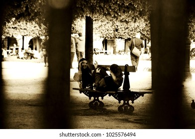 PARIS, FRANCE - MAY 16, 2016: View through blurry park fence bars of girls joyfully workout at Place des Vosges park. In sunny warm days this famous square attracts tourists and locals as well. Sepia.