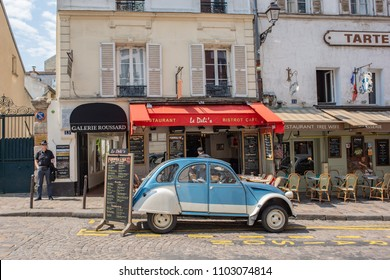 Paris / France - May 16, 2018: A vintage, blue Volkswagon car is parked in front of charming cafes in Place du Tertre, a famous tourist area known for its quaint, historic streets.