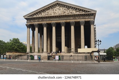 Paris, France - May 16, 2018: People sit on the steps of La Madeleine church on Place Madeleine in Paris, France on May 16, 2018