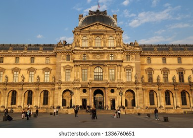Paris, France - May 16, 2018: Tourists walk in front of the Louvre Museum in Paris, France on May 16, 2018