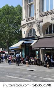 Paris, France - May 16, 2018: People sit at a sidewalk cafe on Rue de la Pepiniere street in Paris, France on May 16, 2018
