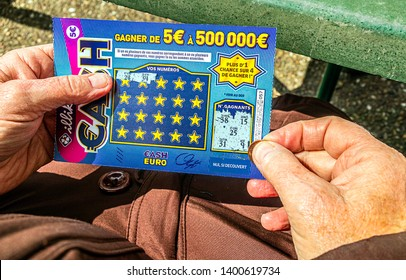 PARIS, FRANCE - MAY 16, 2019. A person seated on the terrace of a bar, scratching a CASH lottery ticket from la Française des Jeux.