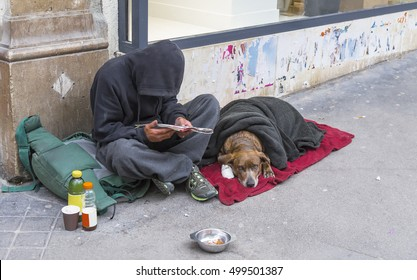 PARIS, FRANCE - MAY 17, 2016: clochard with dog sitting by the wall of the building on the street of Paris. France.