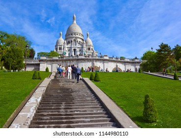 Paris, France - May 17, 2017: Basilica of the Sacred Heart of Paris (Sacre-Cœur Basilica) at the Montmartre with steps leading to it