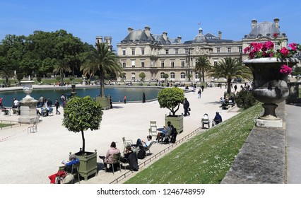 Paris, France - May 17, 2018: People walk in the Luxembourg gardens past the Palais du Luxembourg in Paris, France on May 17, 2018