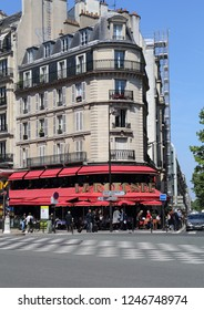 Paris, France - May 17, 2018: Restaurant on a street corner and traffic op cars and pedestrians in Paris, France on May 17, 2018