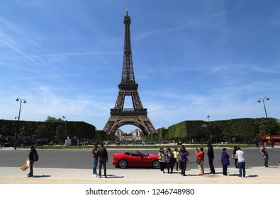 Paris, France - May 17, 2018: Tourists and a red sports car in front of the Eifel tower in Paris, France on May 17, 2018