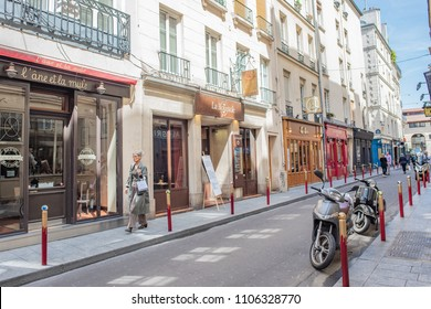 Paris / France - May 18, 2018: A stylish woman wanders the beautiful, quaint, colorful streets of the famous and popular Saint-Germain des Pres neighborhood, in Paris' Left Bank.