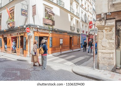 Paris / France - May 18, 2018: People wander the beautiful, quaint, colorful streets of the famous and popular Saint-Germain des Pres neighborhood, in Paris' Left Bank.