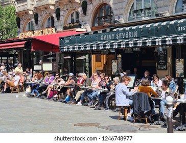 Paris, France - May 18, 2018: People sit on sidewalk cafe on Place Saint-Michel in Paris, France on May 18, 2018