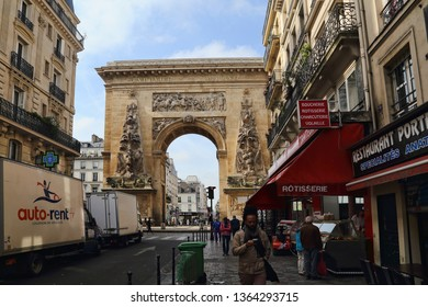 Paris, France - May 18, 2018: People walk in street with shops and restaurants and the historical triumphal arch of Porte Saint-Denis in Paris, France in Paris, France on May 18, 2018