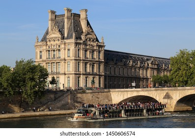 Paris, France - May 18, 2018: Boat with tourists sails past the Louvre museum on the river Seine in Paris, France on May 18, 2018