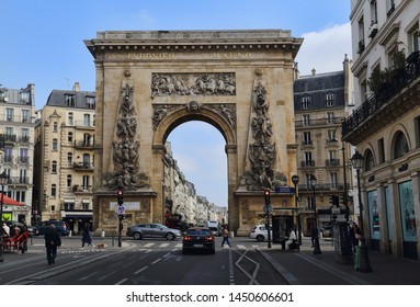 Paris, France - May 18, 2018: Cars and people Rue Saint-Denis and the historical triumphal arch of Porte Saint-Denis in Paris, France in Paris, France on May 18, 2018