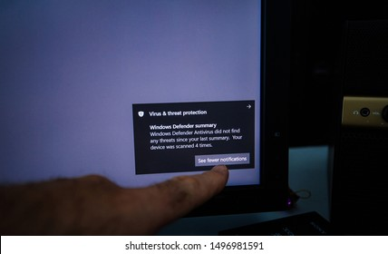 Paris, France - May 18, 2019: man hand pointing to Virus and Threat Protection during Defender antivirus operation on modern Windows 10 computer