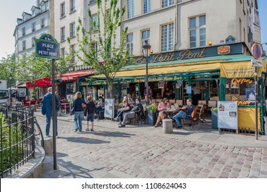 Paris / France - May 19, 2018: People enjoy coffee and wine at the beautiful cafe, Le Petit Pont, located in the San Michel neighborhood, near Notre Dame Cathedral.