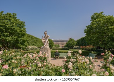 Paris / France - May 19, 2018: An older gentleman sits next to a statue in the garden at the Palais Royal building in Paris' Right Bank.