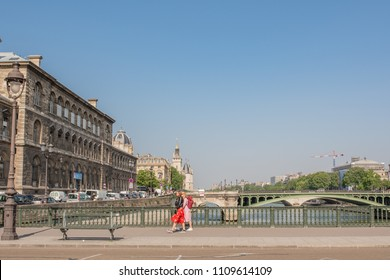 Paris / France - May 19, 2018: Stylish young women in vintage fashion cross the bridge to the Isle de la Cite, the island in the center of Paris, on a sunny spring day.