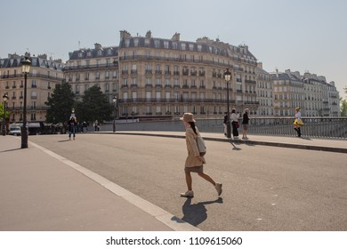 Paris / France - May 19, 2018: A stylish young woman crosses the bridge to the Isle de la Cite, the island in the center of Paris, on a sunny spring morning.