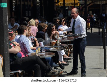 Paris, France - May 19, 2018: Waiter and tourists at a restaurant in Paris, France on May 19, 2018