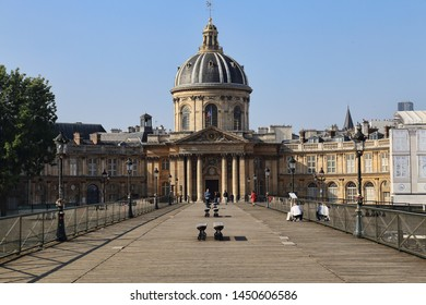 Paris, France - May 19, 2018: People walk on the footbridge to the cultural centre Institut de France in Paris, France on May 19, 2018