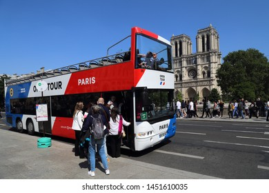 Paris, France - May 19, 2018: Tourists enter a tourist bus near Notre Dame cathedral in Paris, France on May 19, 2018