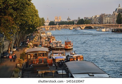 Paris, France - May 19, 2018: Historical boats and people walking along the quay on the river Seine in Paris, France on May 19, 2018