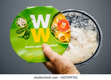 Paris, France - May 19, 2019: Man hand holding Weight Watchers Ricotta Spinach and Tortellini with cheese sauce gray background
