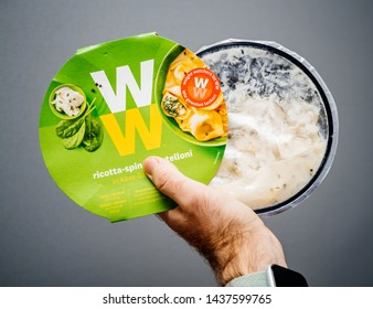 Paris, France - May 19, 2019: Man hand holding Weight Watchers Ricotta Spinach and Tortellini with cheese sauce gray isolated background
