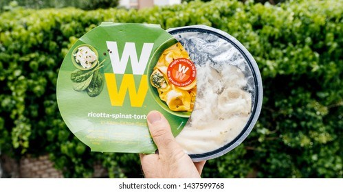 Paris, France - May 19, 2019: Man hand holding Weight Watchers Ricotta Spinach and Tortellini with cheese sauce green garden background