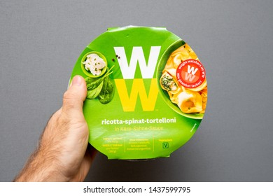Paris, France - May 19, 2019: Man hand holding Weight Watchers Ricotta Spinach and Tortellini with cheese sauce - isolated gray background
