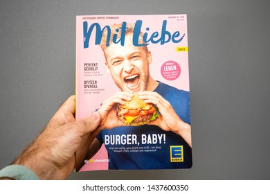 Paris, France - May 19, 2019: Man hand holding Mit Liebe magazine published by Edeka Supermarket featuring happy man eating a delicious hamburger