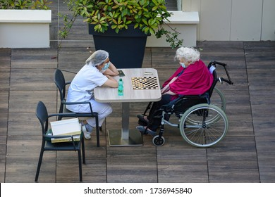 PARIS, FRANCE - MAY 20, 2020: nurse playing checkers with an elderly and disabled woman in a nursing home during the coronavirus pandemic Covid-19. Both wear a protective face mask.
