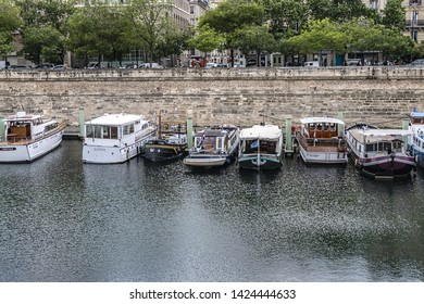 PARIS, FRANCE - MAY 21, 2019: Canal Saint Martin in Paris and row of docked houseboats. Canal Saint Martin is a 4,5 km long canal, it connects canal de l'Ourcq to River Seine.