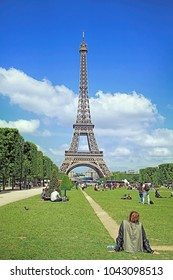 PARIS, FRANCE - MAY 22, 2015: A girl sitting at the Mars Fields looking at the Eiffel Towercaptured on spring, on May 22 in Paris, France