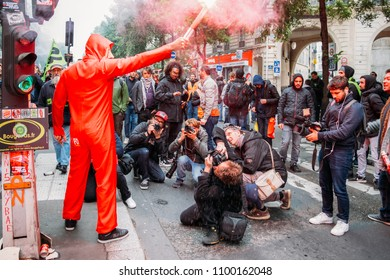 Paris, France - May 26, 2018: Protestors wearing a Guy Fawkes mask light gas canisters to express their anger against French President Macro's government, among other issues, on the streets of Paris