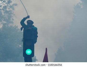 Paris, France - May 26, 2018: Protestor climbs a traffic light to express his anger against French President Macro's government, among other issues, on the streets of Paris