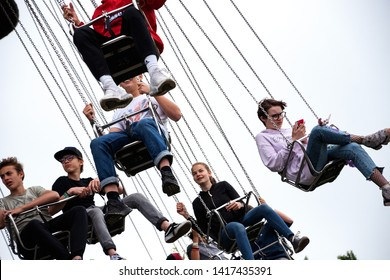 PARIS, FRANCE - May 26, 2019: Teens have fun riding Chain Carousel at Jardin d'Acclimatation, popular children's amusement park located in Bois de Boulogne. Girl checking and posting in social media.